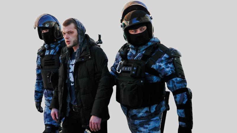 شرطيان يعتقلان أحد المتظاهرين.  أ.ب