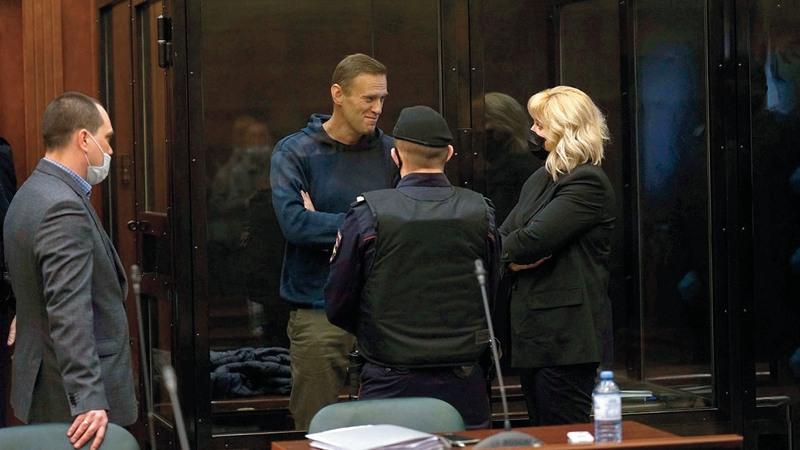 نافالني يتحدث إلى أحد محاميه خلال جلسة الاستماع لأقواله.  أ.ب