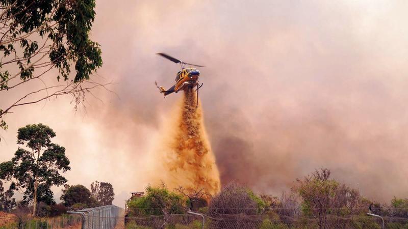المروحيات تشارك في إطفاء النيران.   إي.بي.إيه