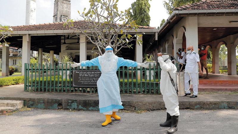 عامل صحي يُعقم زميله للوقاية من «كورونا» في سريلانكا.   أ.ب