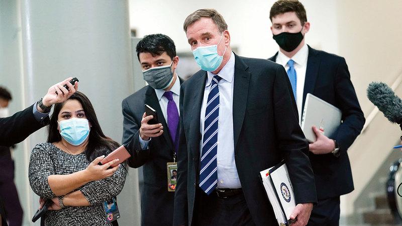 السيناتور الديمقراطي مارك وارنر، يتبعه الصحافيون أثناء سيره في مبنى الكابيتول، بعد انتهاء اليوم الثالث من محاكمة ترامب.  أ.ب