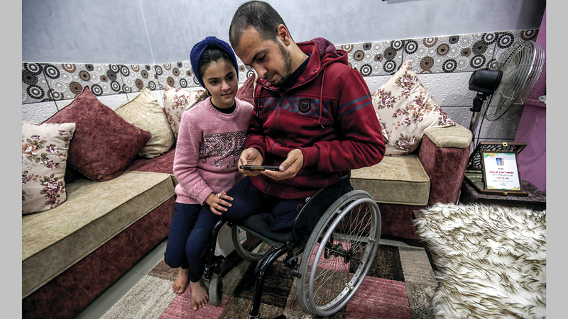 محمد أبوجزر يعرض على ابنته (ميسم) صور أطفاله الذين استشهدوا في حرب 2014 على غزة.   أ.ف.ب