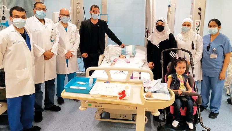 «منيرة» مع الفريق الطبي وأسرتها.. وتظهر أختها في الصورة مريضة بالمرض نفسه.  من المصدر