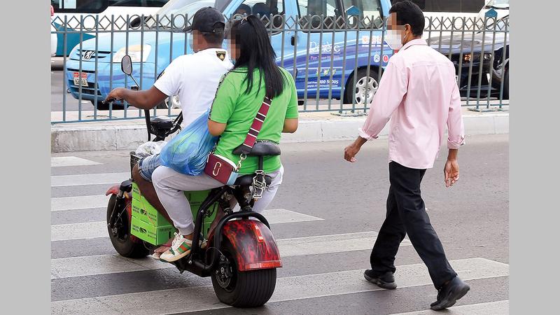 شاب يستخدم الدرّاجة في توصيل راكبة. تصوير: إريك أرازاس