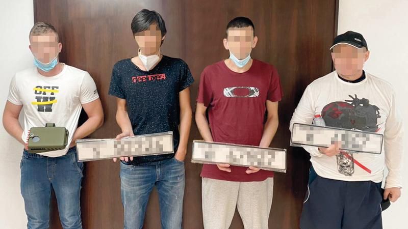 أفراد العصابة بعد القبض عليهم يحملون اللوحات المزورة.  من المصدر