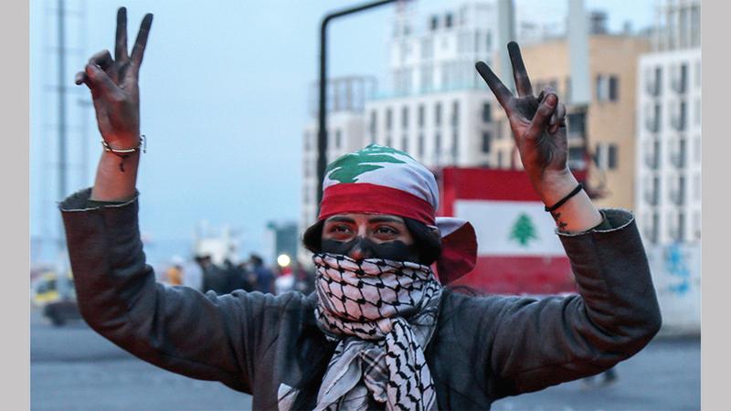 إحدى المتظاهرات ترفع علامة النصر في بيروت. إي بي.إيه