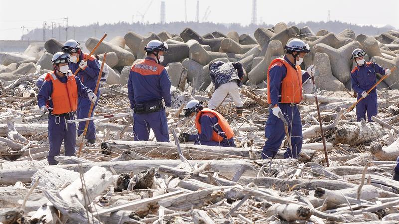 رجال الدفاع المدني يجرون عمليات بحث عن رفات المفقودين.  إي.بي.إيه