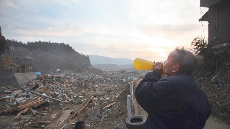ساتو يدعو السكان المتبقين إلى العمل على إعادة بناء القرية.   من المصدر