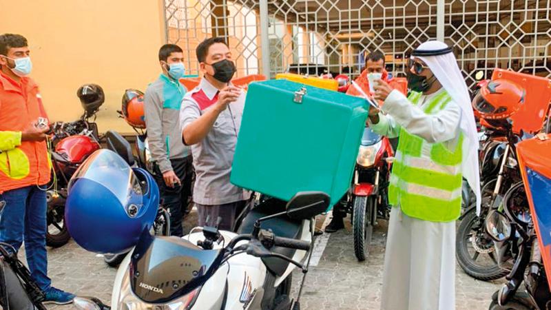 مفتش «طرق دبي» خلال تنفيذ الحملة على «ديلفري».                من المصدر