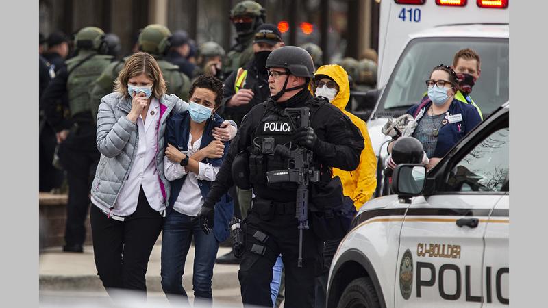 عمال الرعاية الصحية يخرجون من المتجر بعد أن فتح المسلح النار في بولدر بولاية كولورادو.   أ.ف.ب