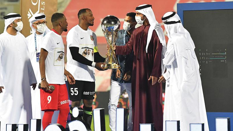 راشد بن حميد يسلّم كأس الخليج العربي إلى قائد شباب الأهلي ماجد ناصر. À الإمارات اليوم