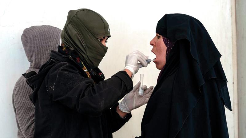 طبيبة من قوات سورية الديمقراطية تأخذ عينات من الحمض النووي لسكان المخيم.  من المصدر