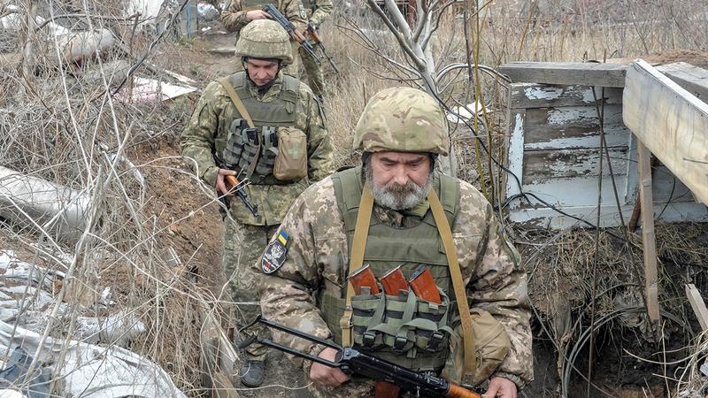 أفراد من القوات الأوكرانية في مواقعهم القتالية على الخط الفاصل بينهم وبين الثوار الموالين لروسيا.   رويترز