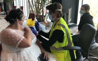 الصورة: أمريكية تتلقى اللقاح بفستان الزفاف
