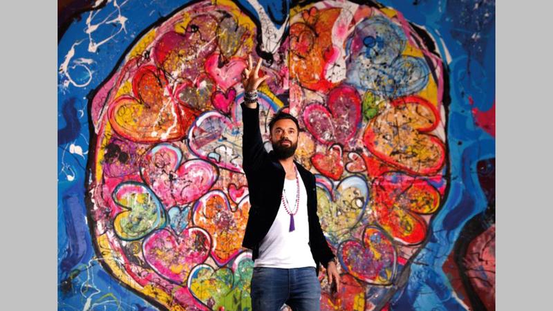 الرسام العالمي ساشا جفري يقدم عرضاً حياً في المزاد.   وام