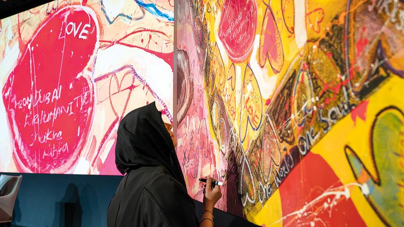لطيفة بنت محمد توقّع على لوحة «الطريق إلى رحلة الإنسانية».  تصوير: مصطفى قاسمي