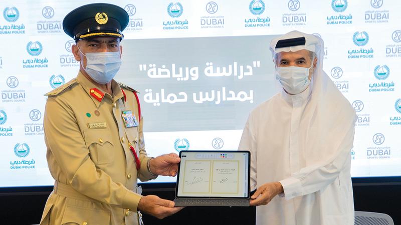 سعيد حارب واللواء محمد بن فهد خلال توقيع الاتفاقية.  من المصدر