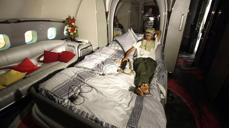 أحد الثوار الليبيين ينام على سرير القذافي في الطائرة.                من المصدر