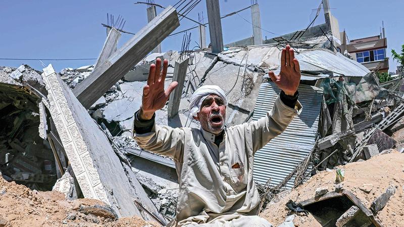 فلسطيني يجلس أمام أنقاض منزله المدمّر جنوب غزة.   أ.ف.ب