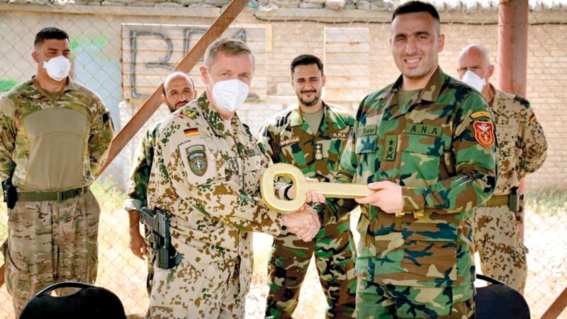 مراسم تسليم وتسلّم بين القوات الألمانية وقوات أفغانية لمعسكر مايك سبان في مزار الشريف.     رويترز