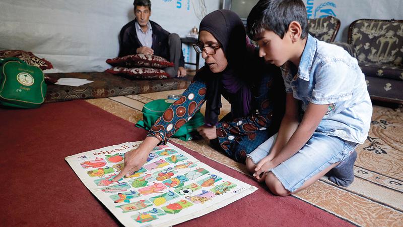 «أم محمد» تحاول مساعدته على التعلم كلما أمكن ذلك.   أ.ف.ب