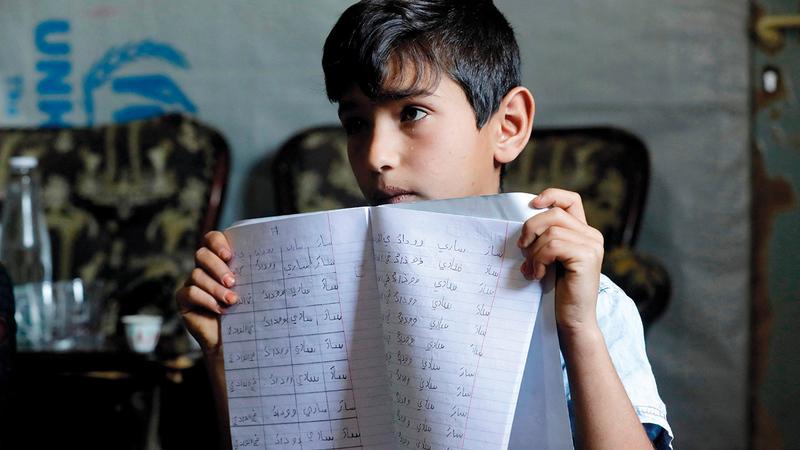 محمد يعرض كراسته للغة العربية.   أ.ف.ب