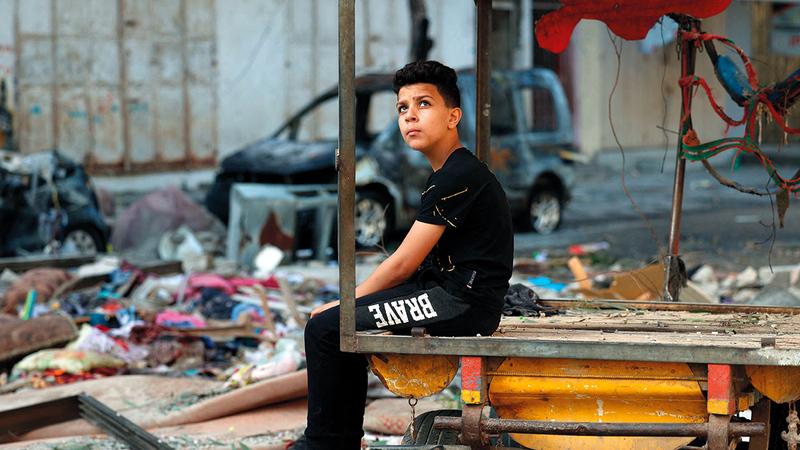 الذهول والصدمة يبدوان عل وجه طفل فلسطيني وهو يعاين الدمار الذي لحق بالمكان جراء ضربة جوية إسرائيلية.   أ.ف.ب