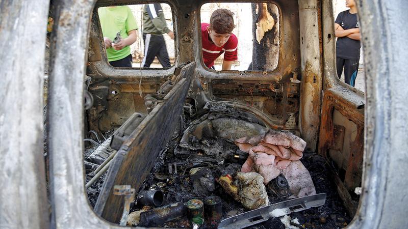 طفل فلسطيني يبدو مذهولاً وهو يلقي نظرة على سيارة محترقة تعرضت لقذيفة إسرائيلية.  أ.ب