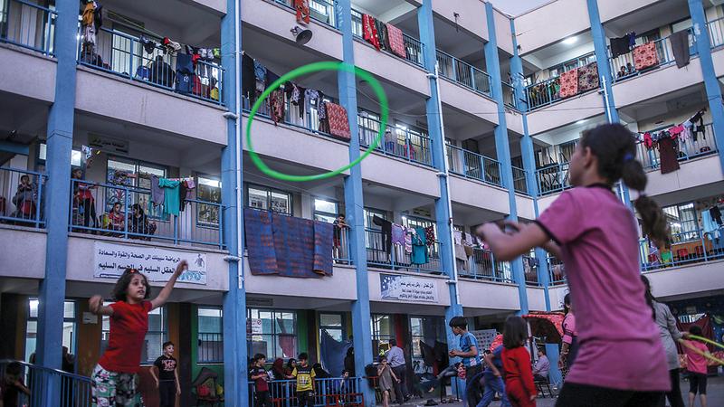 أطفال يلعبون في فناء إحدى مدارس وكالة «أونروا» التي لجأت إليها آلاف العائلات الفلسطينية بحثاً عن الأمان.  إي.بي.إيه