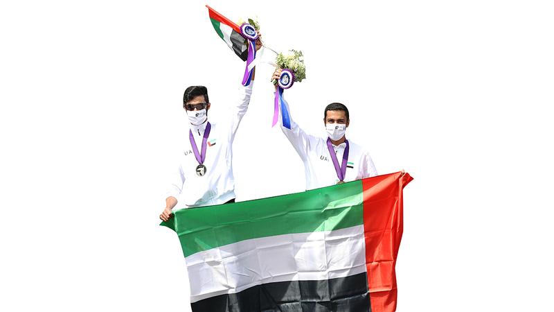 سالم ملهوف ومنصور الفارسي يرفعان علم الإمارات على منصة التتويج.   من المصدر