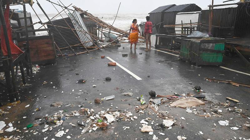 مواطنان هنديان يراقبان مياه البحر الهائجة وسط الحطام.   أ.ف.ب