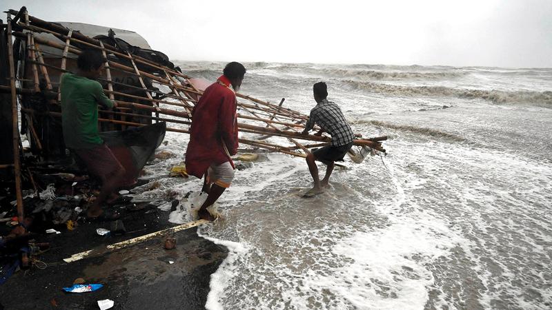 مواطنان هنديان يحاولان إنقاذ ما تبقى لهما من ممتلكات.   أ.ف.ب
