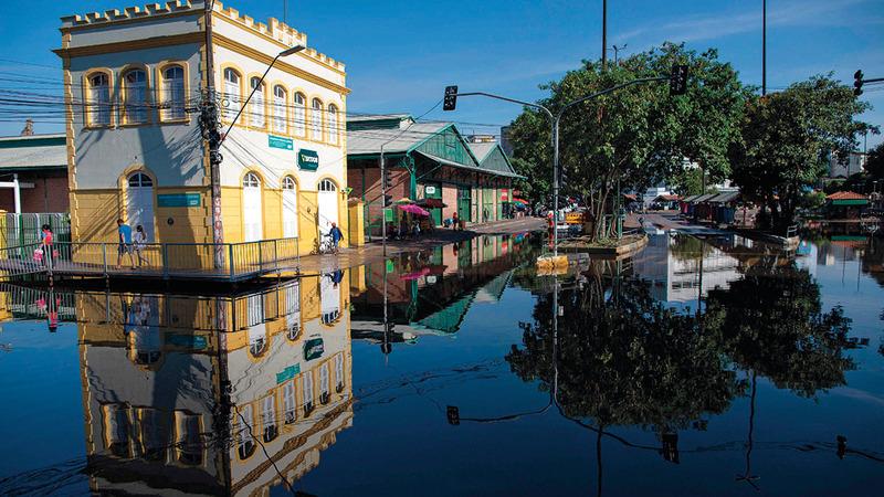 الناس يسيرون فوق ممرات مؤقتة أقيمت في الشوارع تفادياً لمياه الفيضان.  أ.ف.ب