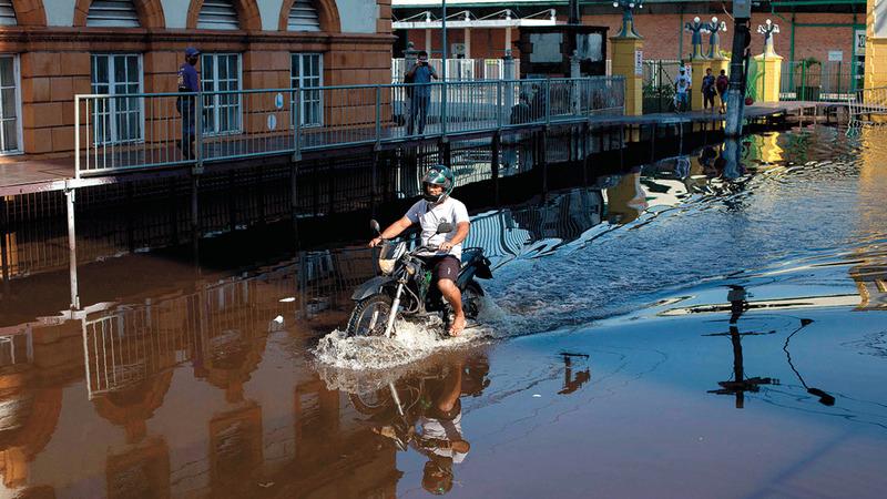يقود دراجته النارية وسط مياه الفيضان.  أ.ف.ب