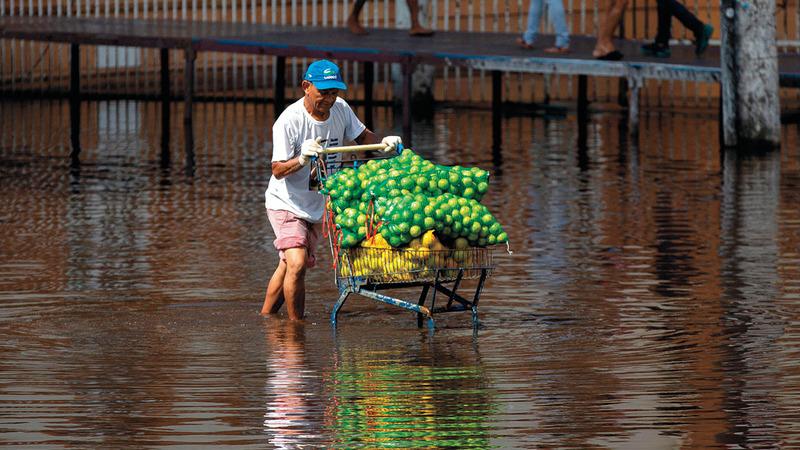 يواجه صعوبة في تحريك عربته المملوءة بالفواكه وسط شارع غمرته المياه.   أ.ف.ب