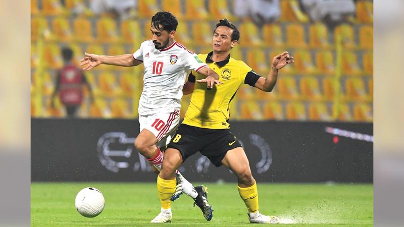 خلفان مبارك يحاول السيطرة على كرته وسط مراقبة من لاعب ماليزيا.  تصوير: أسامة أبوغانم