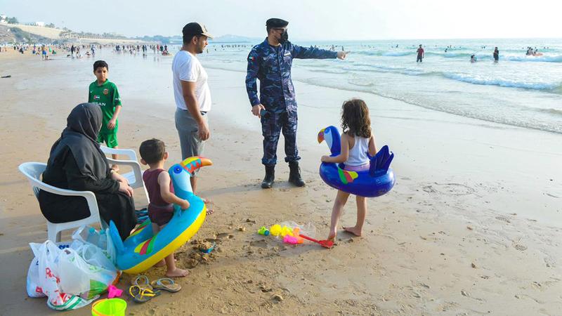 شرطي يشرح الإرشادات الآمنة لإحدى الأسر على الشاطئ. الإمارات اليوم