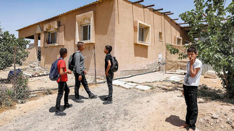 عدد من الصبية يلعبون خارج بيوتهم المسقوفة بالصفيح في قرية صوانين.  أ.ف.ب