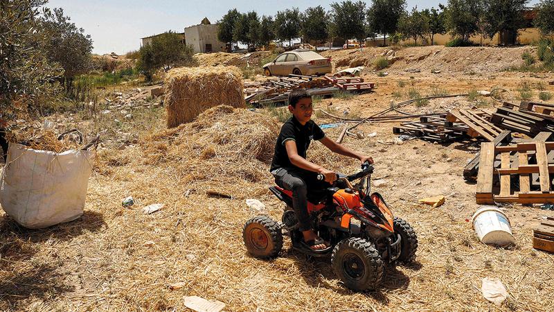 طفل يلهو على دراجة نارية في إحدى ساحات القرية الترابية التي تعاني انعداماً في الخدمات.  أ.ف.ب