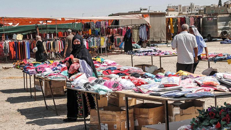 الناس يتسوقون في سوق أقيمت في الهواء الطلق في قرية رهط جنوب النقب.  أ.ف.ب