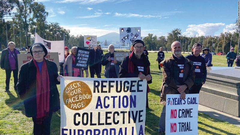 ناشطو حقوق المهاجرين يتجمّعون خارج مبنى البرلمان الأسترالي في كانبيرا مطالبين بمنح العائلة وضع اللاجئ.  من المصدر