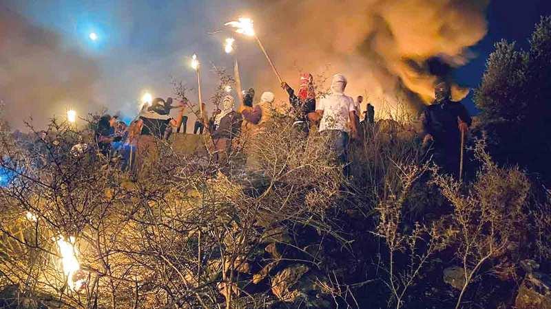 سكان «بيتا» يدافعون عن أرضهم وجبلهم بالإرباك الليلي.  الإمارات اليوم