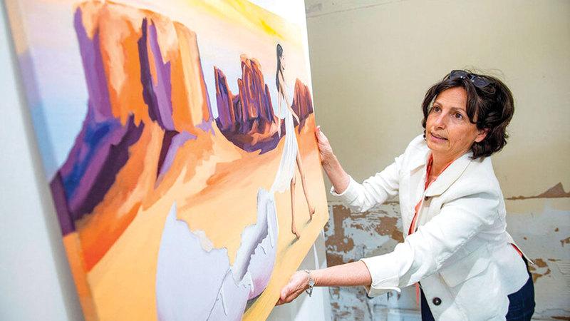 باربرا تزيح إحدى اللوحات المباعة في الشارع.   من المصدر