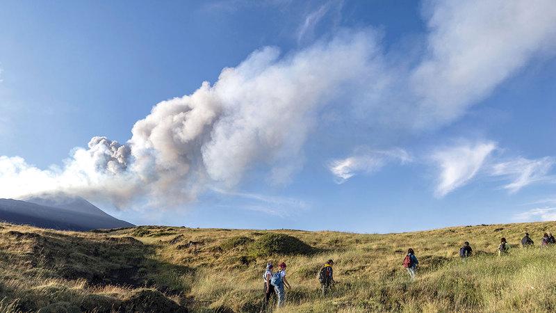 متسلقون يسيرون قبالة البركان الذي عاود الانفجار.  أ.ب