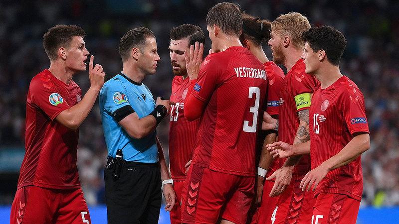 لاعبو الدنمارك يعترضون على الحكم الهولندي داني ماكيلي بعد احتسابه ضربة جزاء لإنجلترا.  أ.ف.ب