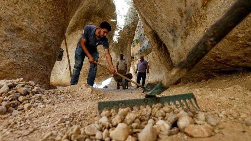 عدد من العمال انتهوا من عملية قشر الأرضية لتسويتها ورصفها بأحجار قديمة.  أ.ف.ب
