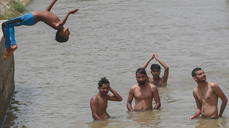 أطفال يطفئون الحرارة الشديدة بالاستحمام في إحدى القنوات بسري جانجانجار شمال الهند.   أ.ف.ب