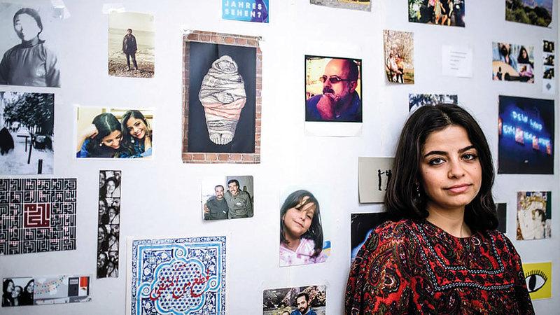 «وفاء» أمام لوحة تعرض صور عائلتها.  من المصدر