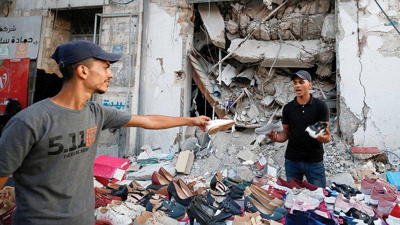 يتحسر محمد القصاص على الدمار الذي لحق بمحل الأحذية الذي يملكه خلال القتال بعد أن أصبح يبيع ما استطاع انتشاله من أحذية من وسط الركام.   رويترز