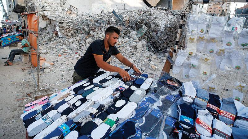 بائع ملابس فلسطيني يبيع بضاعته وسط أنقاض المباني المدمرة.   أ.ف.ب ورويترز